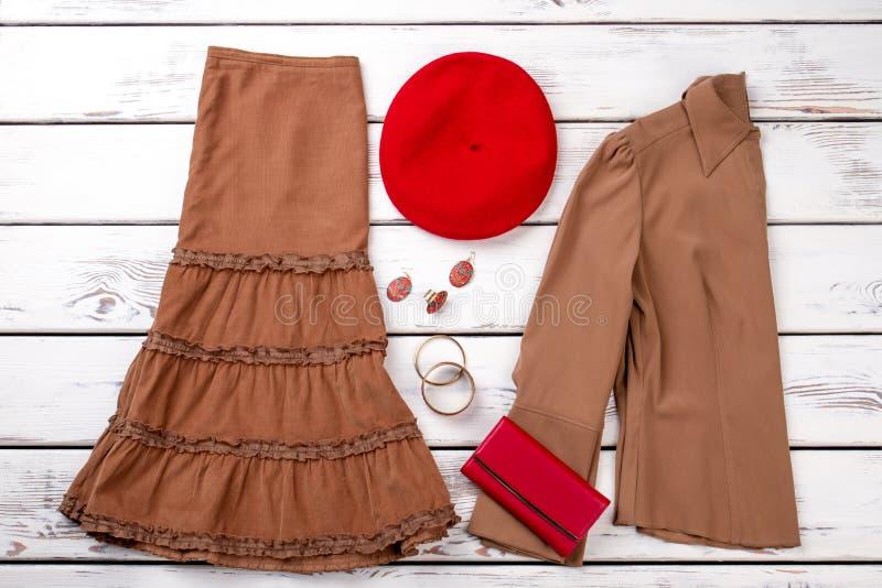 布朗衣裳、红色钱包和berete帽子 图库摄影