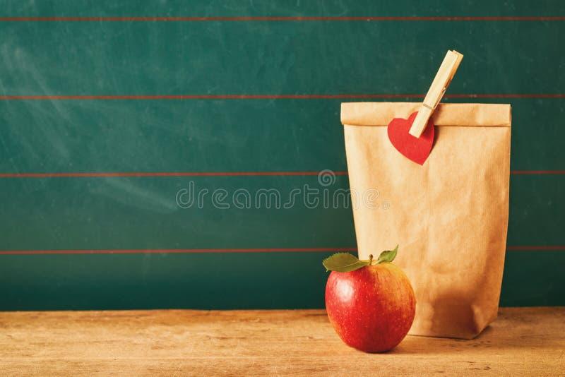 布朗袋子午餐和红色苹果 免版税图库摄影