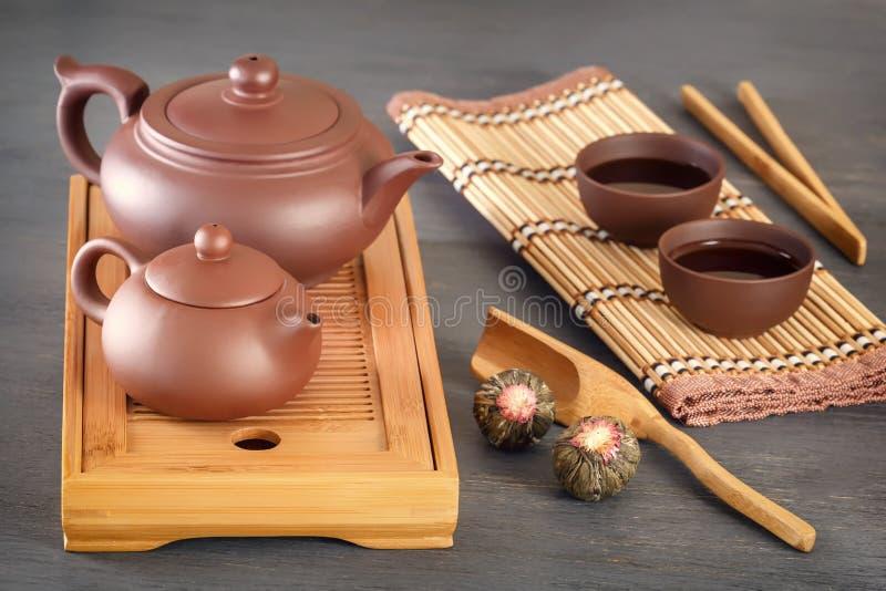 布朗陶瓷茶壶和杯子在为传统亚洲茶道准备的一个特别木茶盘 库存图片