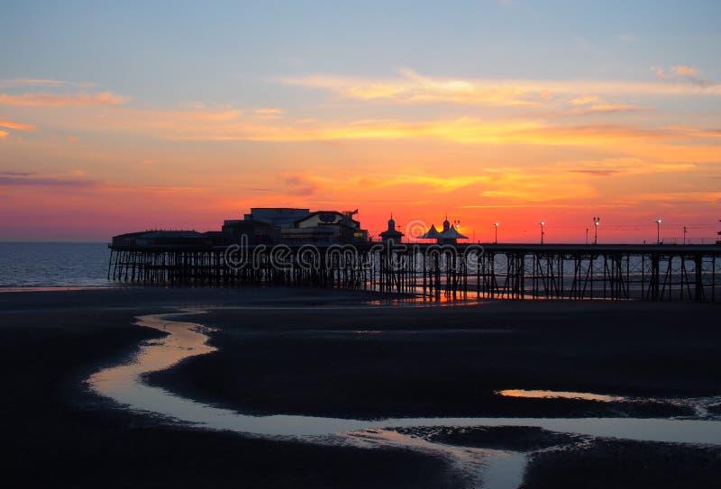 布莱克浦北部码头风景看法在发光的红色平衡在日落之后的光与被阐明的桃红色和黄色天空和云彩 库存照片