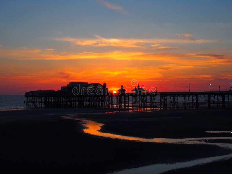布莱克浦北部码头风景看法在发光的红色晚上光的在与有启发性桃红色和黄色天空和云彩的日落 免版税库存照片