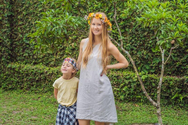 布裙、全国巴厘语衣物和他的母亲的男孩游人有在他的头的一个花圈的 图库摄影