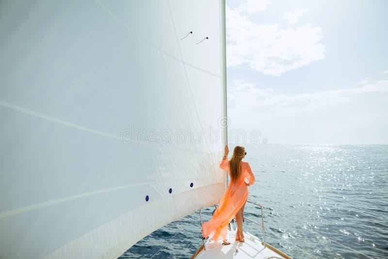 布裙乘快艇的白色风帆豪华旅行的妇女 免版税库存图片