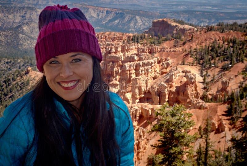 布赖斯峡谷的美丽的微笑的妇女在与蓝色外套和紫色编织帽子的冬天 库存图片