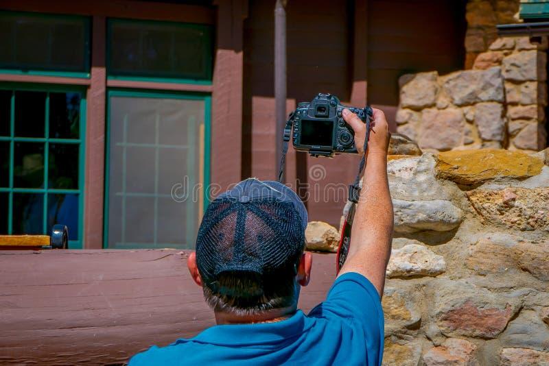 布赖斯峡谷,犹他, 2018年6月, 07日:供以人员穿舒展胳膊的一件黑帽会议和蓝色衬衣拍a的照片 图库摄影