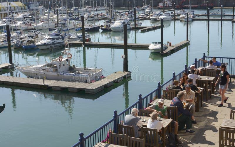 坐在餐馆大阳台的小船在小游艇船坞和人们.布赖顿.东萨塞克斯郡.
