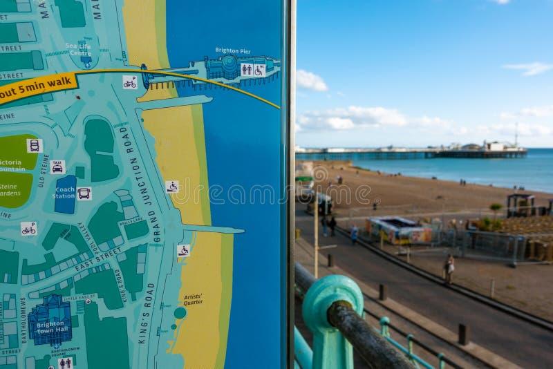 布赖顿,英国1 2018年10月:亚洲年轻旅客阅读和指向在委员会的布赖顿市镇和布赖顿码头地图 库存图片