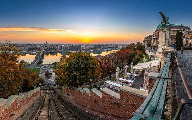 布达佩斯、匈牙利-布达佩斯城堡小山缆索铁路的Budavari Siklo轨道和布达城堡日出的奥斯陆王宫 库存图片