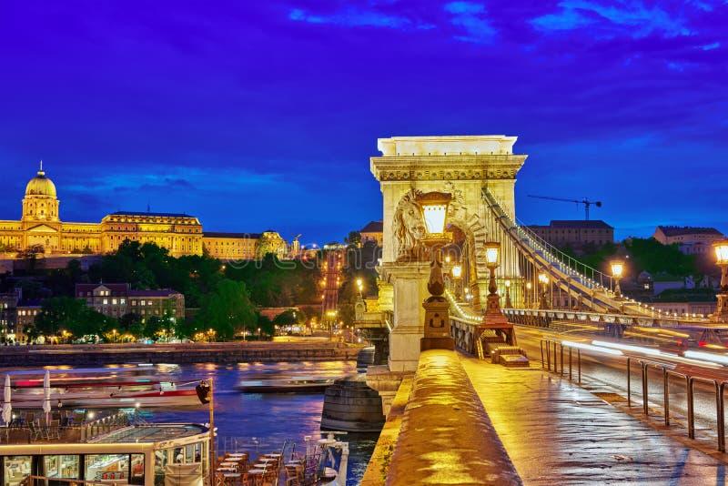 布达佩斯皇家城堡和Szechenyi铁锁式桥梁在黄昏计时fr 图库摄影