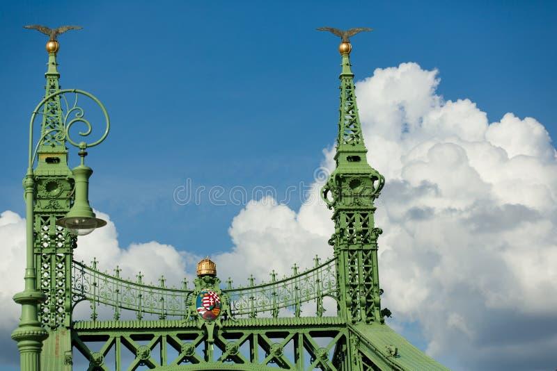 布达佩斯著名自由桥梁细节,绿化被绘的铁基地、冠和盾有冠的和金黄苹果与鸟 免版税库存照片