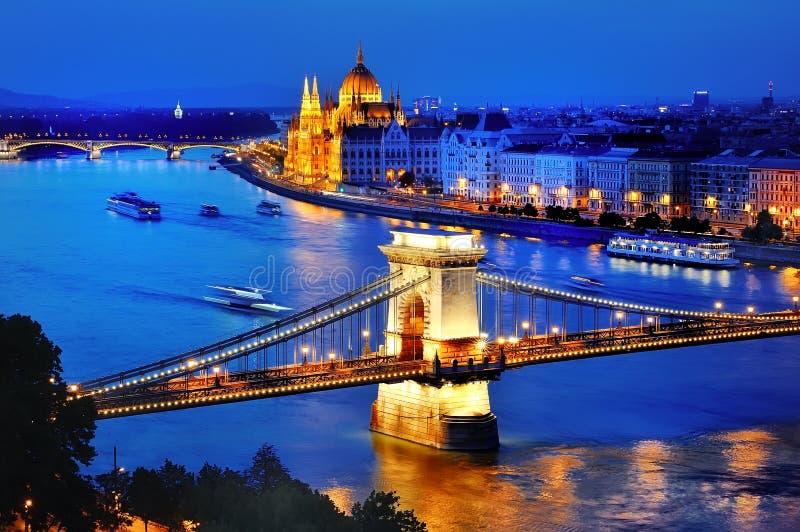 布达佩斯,匈牙利全景,有多瑙河、铁锁式桥梁和议会的在蓝色小时 库存图片