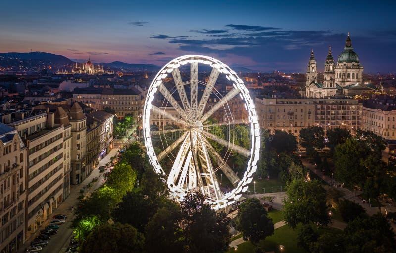 布达佩斯,匈牙利-伊丽莎白广场鸟瞰图黄昏的与有启发性弗累斯大转轮、圣斯蒂芬的大教堂和议会 库存照片