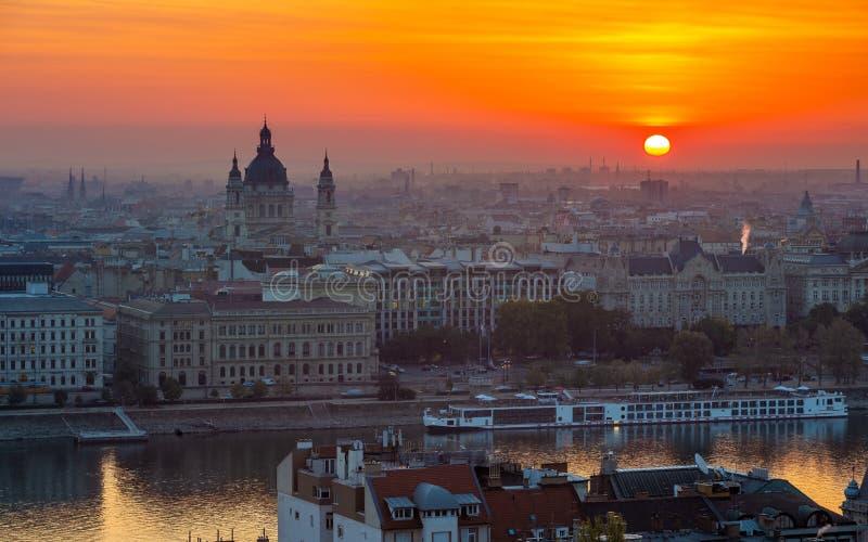 布达佩斯,匈牙利-在布达佩斯的美好的金黄日出和圣斯蒂芬的Basilca,在河多瑙河的游轮 免版税库存图片