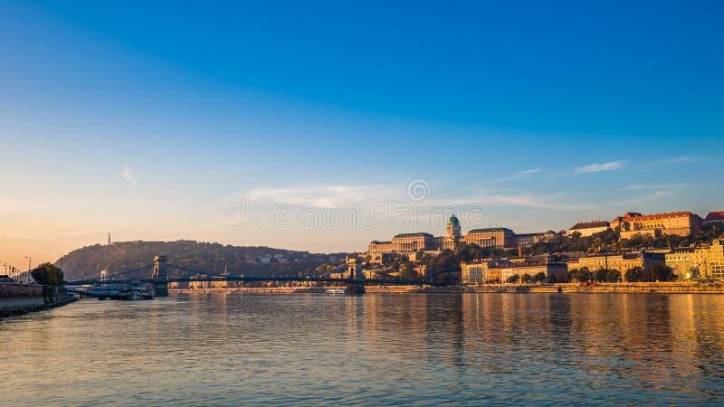布达佩斯,匈牙利-在河多瑙河的金黄日出有Szechenyi铁锁式桥梁的,布达城堡王宫 库存图片