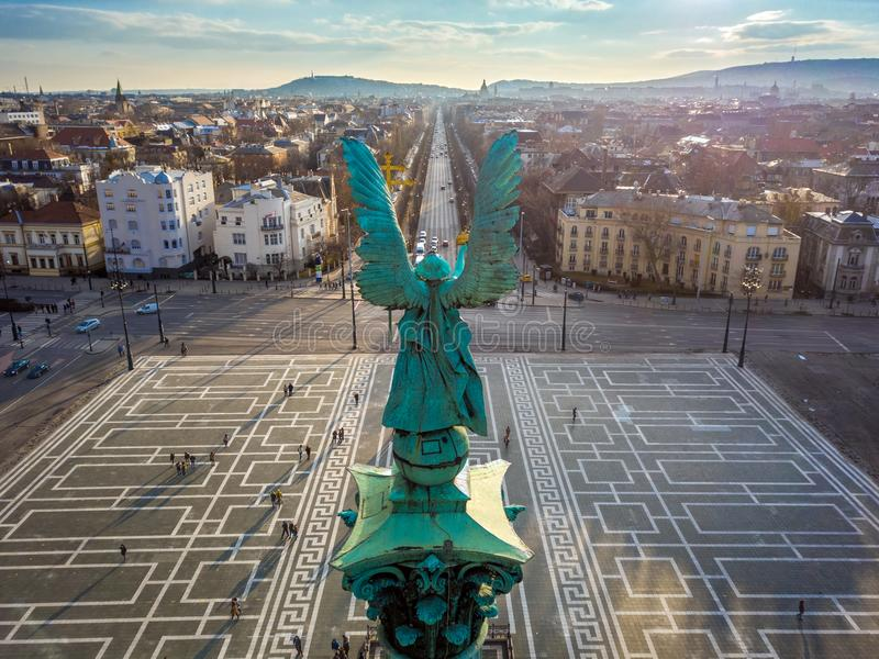 布达佩斯,匈牙利-天使雕塑从后面在英雄在日落的`正方形上面  免版税库存图片