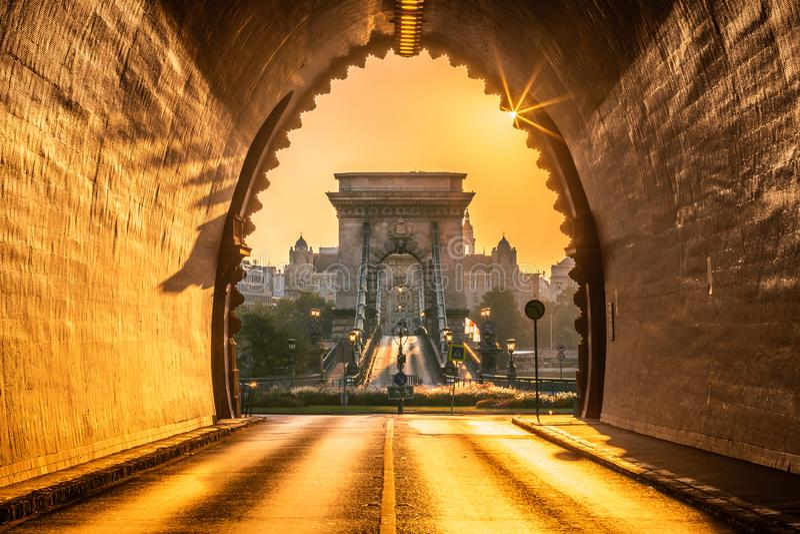 布达佩斯,匈牙利-布达城堡隧道的入口在日出的与空的Szechenyi铁锁式桥梁 免版税库存图片