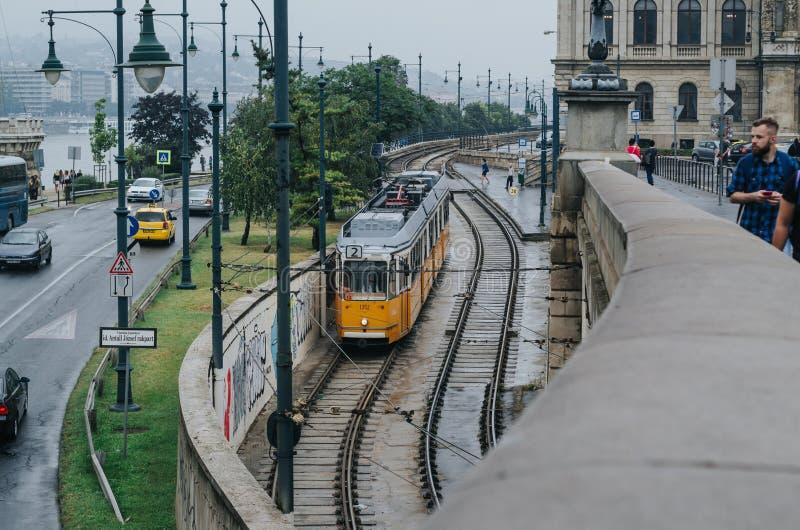 布达佩斯,匈牙利- 2016年9月17日:在铁路的电车和公共汽车、汽车和出租汽车在路,徒步走的人们 不同 库存图片
