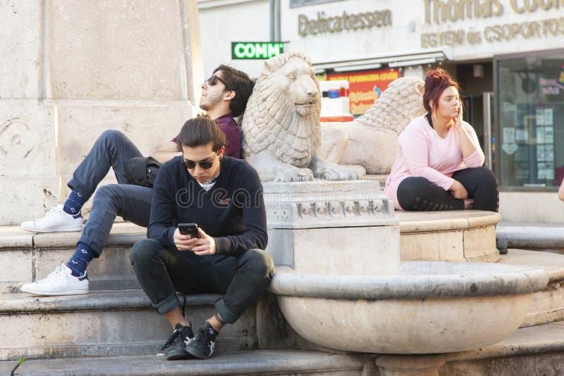 布达佩斯,匈牙利- 2018年4月10日:放松在城市街道上的年轻人 图库摄影