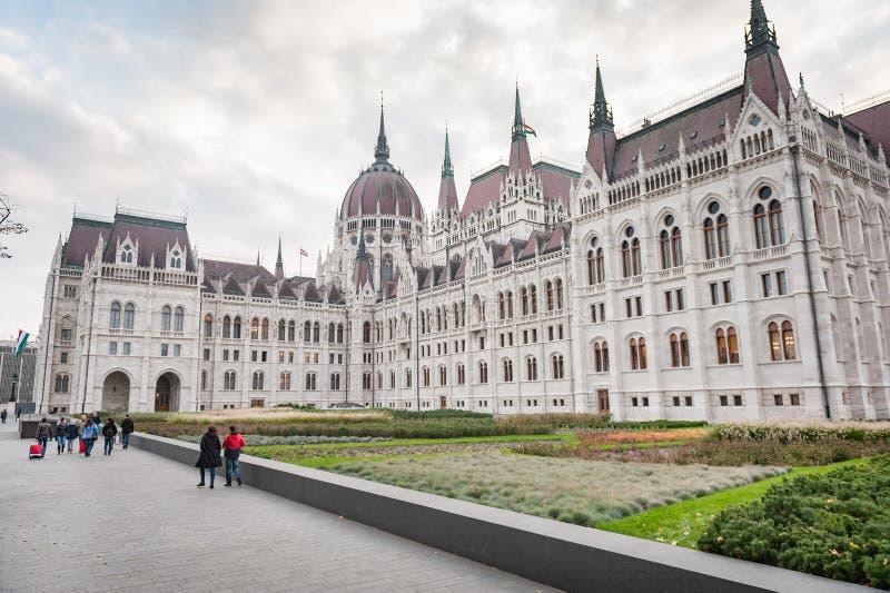 布达佩斯,匈牙利- 2015年10月26日:议会大厦在布达佩斯,有某些当地人的匈牙利在背景中 库存图片