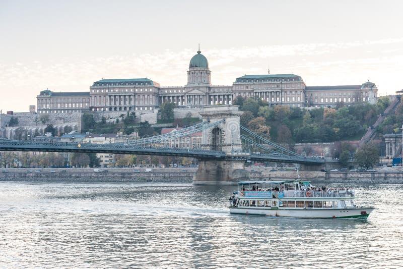 布达佩斯,匈牙利- 2015年10月30日:铁锁式桥梁、多瑙河和王宫在布达佩斯,匈牙利 晚上照片写真 免版税库存图片