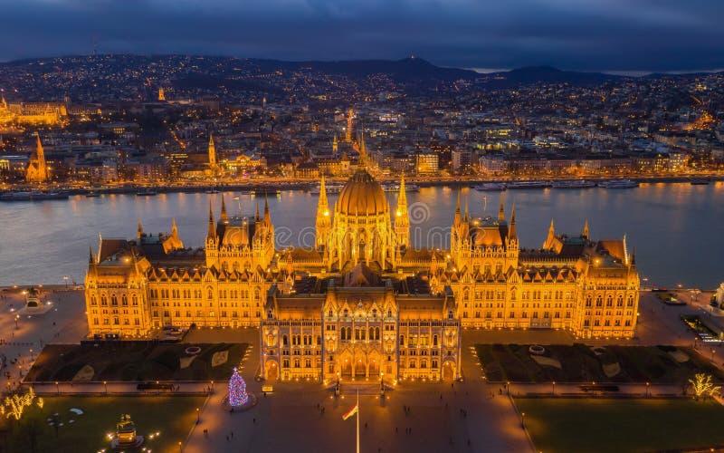 布达佩斯,匈牙利-有启发性匈牙利议会大厦的鸟瞰图在与圣诞树和Buda小山的金黄小时 库存图片