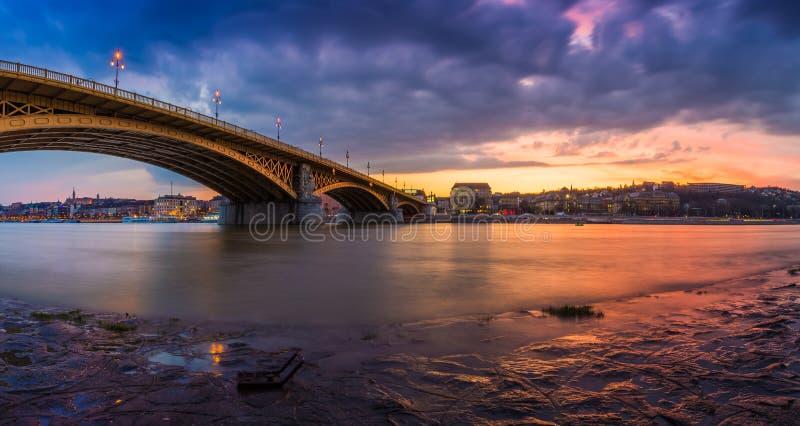 布达佩斯,匈牙利-美丽的五颜六色的日落和云彩的全景射击在玛格丽特桥梁 库存图片