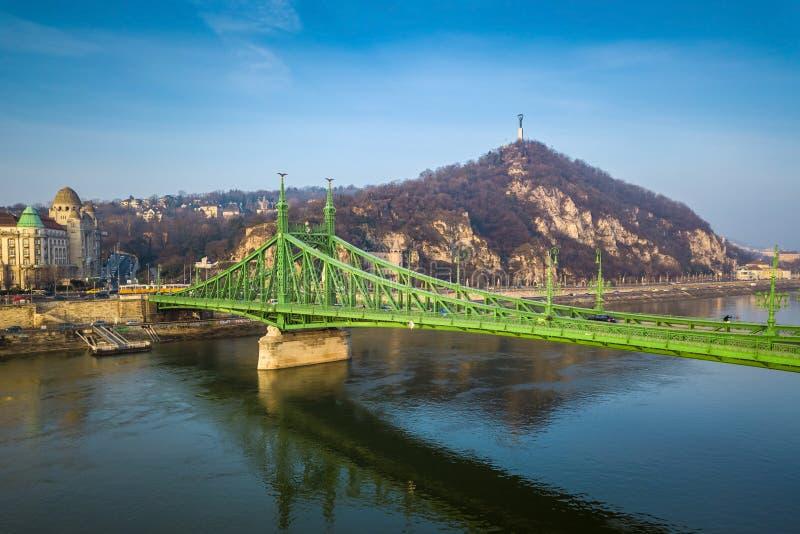 布达佩斯,匈牙利-美丽的自由桥梁Szabadsag暗藏的和传统黄色匈牙利电车 免版税库存照片