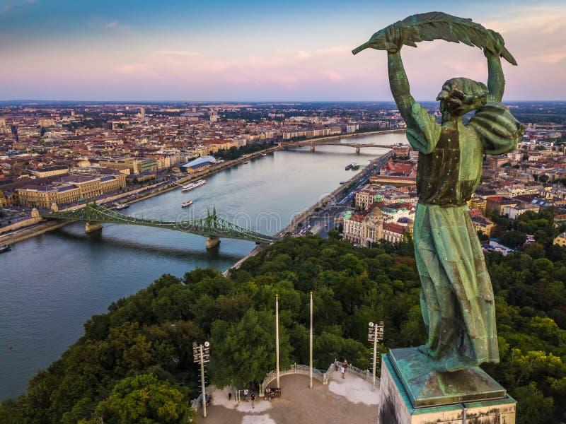 布达佩斯,匈牙利-自由女神像的鸟瞰图在日落的与布达佩斯地平线  免版税库存图片