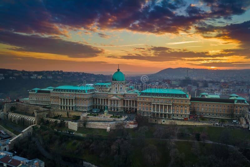 布达佩斯,匈牙利-著名布达城堡王宫的空中全景日落的与惊人的五颜六色的天空 免版税图库摄影