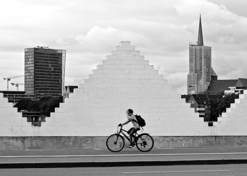 布里曼,德国- 2018年8月14日, -男孩在边路骑他的自行车,当通过一个白色三角型砖墙fra时 免版税库存照片
