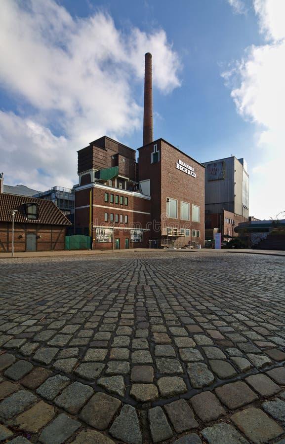 布里曼,德国- 2018年4月15日, -贝克` s与鹅卵石街道的啤酒厂大厦在前景广角射击 库存图片