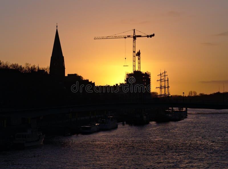 布里曼,德国-有圣马蒂尼鸡尾酒教会和工地工作的河Weser有大起重机的现出轮廓反对日出 免版税图库摄影