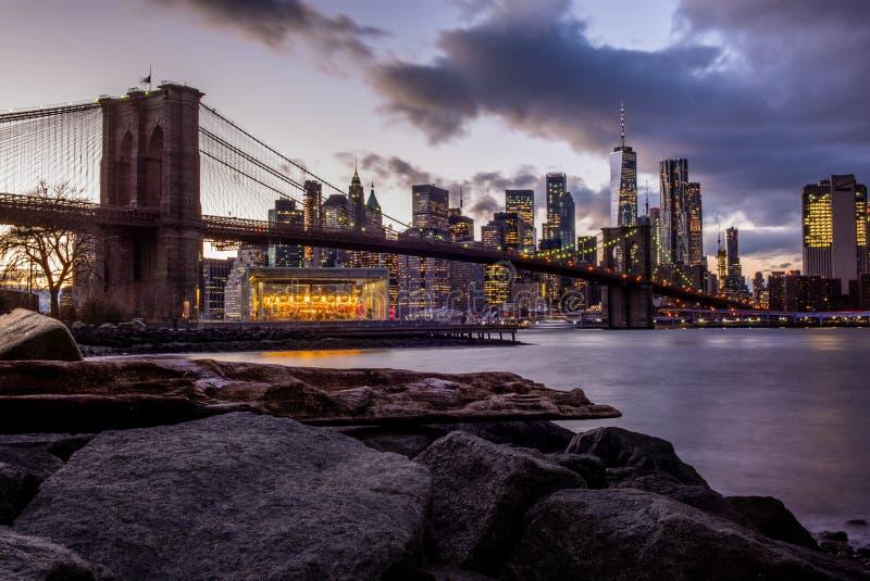布鲁克林大桥和曼哈顿从河沿East河在日落- 1的看法 免版税图库摄影