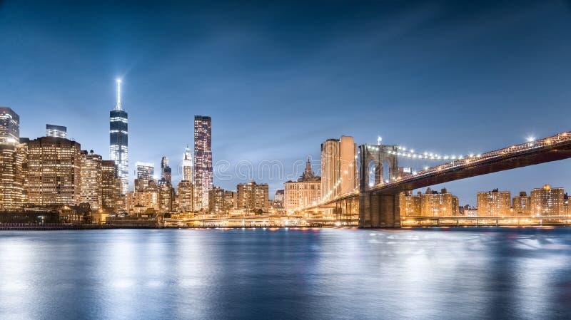 布鲁克林大桥和自由在晚上,更低的曼哈顿,从布鲁克林大桥公园的看法耸立在纽约 库存照片