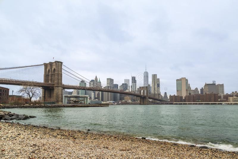 布鲁克林大桥和降低曼哈顿从在布鲁克林,纽约贩卖海滩 免版税图库摄影