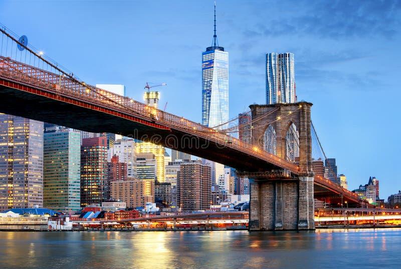 布鲁克林大桥和WTC自由在晚上,纽约耸立 图库摄影