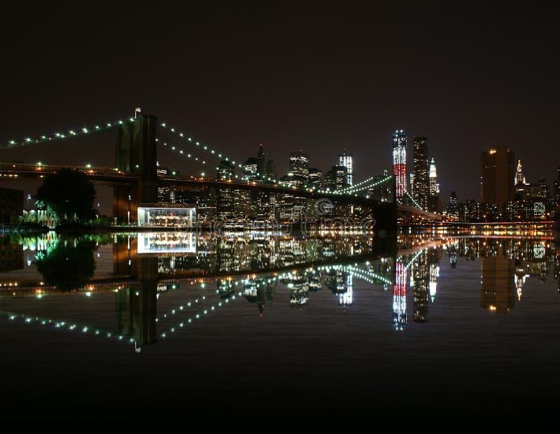 布鲁克林大桥在夜之前在East河和纽约地平线反射 自由塔 免版税库存照片