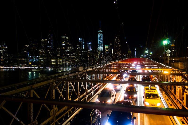 布鲁克林大桥在纽约在与汽车通过的晚上 免版税库存照片