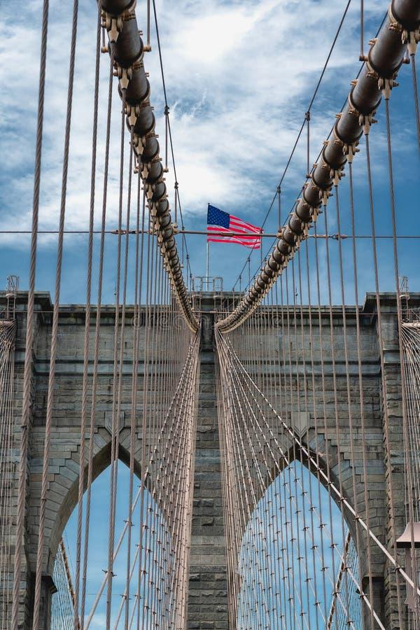 布鲁克林大桥,纽约 美国国旗,多云天空蔚蓝,垂直的横幅 库存照片
