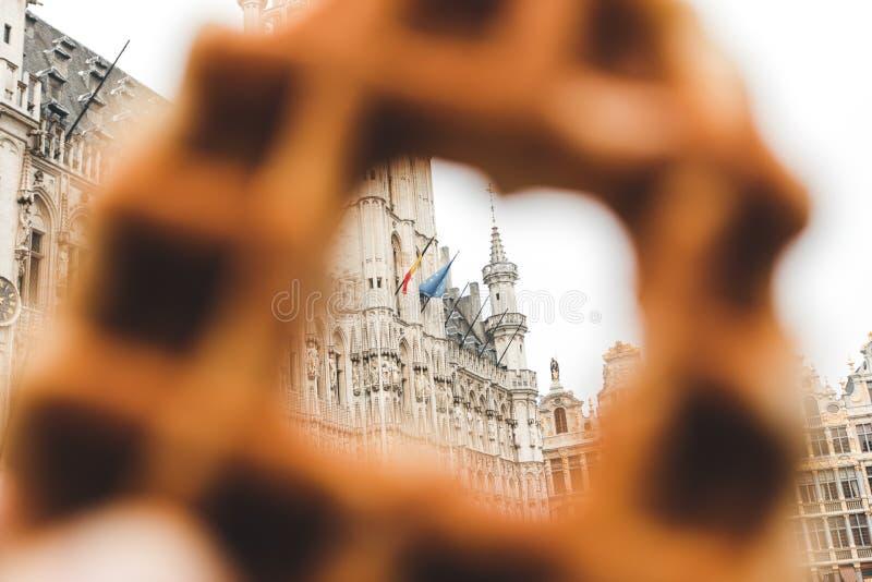 布鲁塞尔城镇厅看法布鲁塞尔大广场的在布鲁塞尔通过在传统比利时华夫饼干的一个孔 免版税库存照片