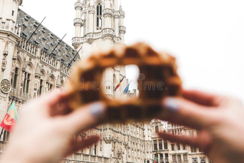 布鲁塞尔城镇厅看法布鲁塞尔大广场的在布鲁塞尔通过在传统比利时华夫饼干的一个孔 库存图片