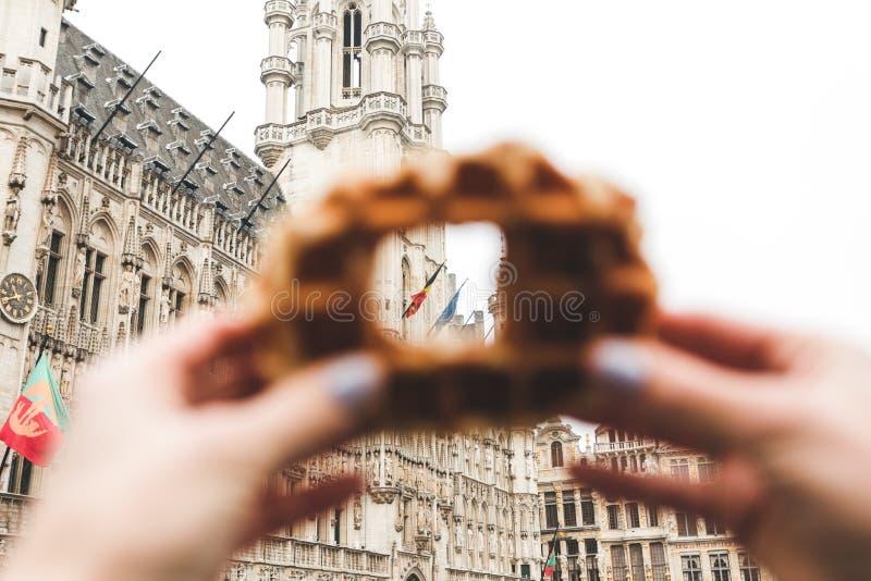 布鲁塞尔城镇厅看法布鲁塞尔大广场的在布鲁塞尔通过在传统比利时华夫饼干的一个孔 免版税图库摄影