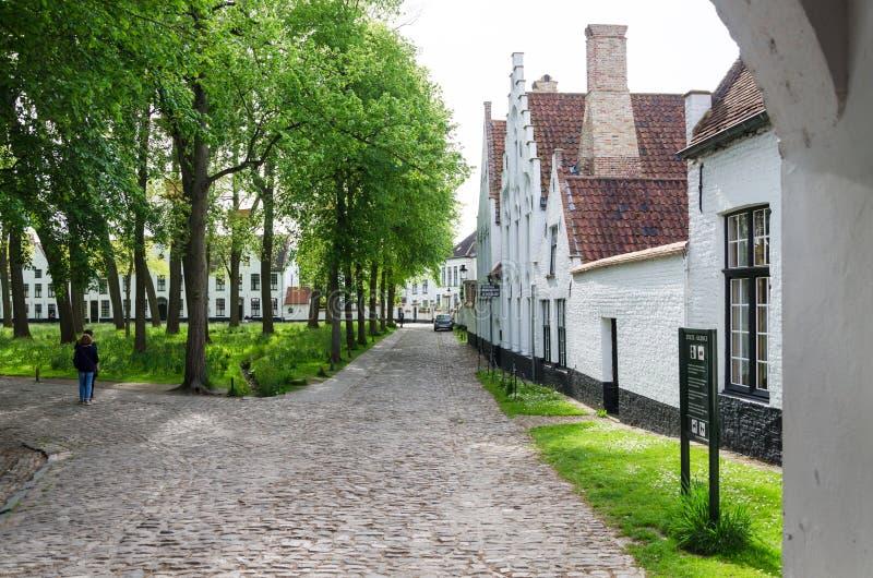 布鲁日,比利时- 2015年5月11日:人们在布鲁日,比利时参观Beguinage的白色房子 免版税库存照片
