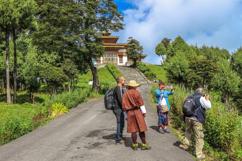 廷布,不丹- 2016年9月10日:拍照片的游人在Druk Wangyal Lhakhang寺庙, Dochula通行证,不丹附近 免版税库存图片