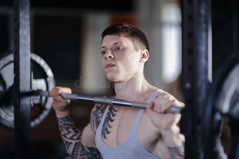帅哥举的重量-杠铃-在健身房 库存照片