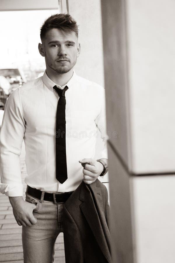 帅哥佩带的衬衣和领带和举行夹克画象  库存照片