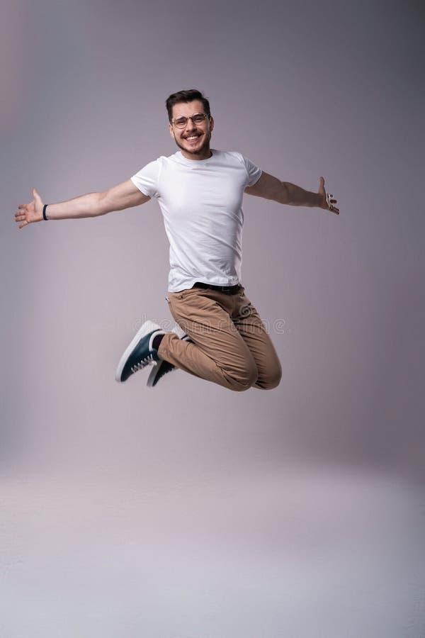 帅哥便服庆祝和跳跃在灰色背景 库存照片