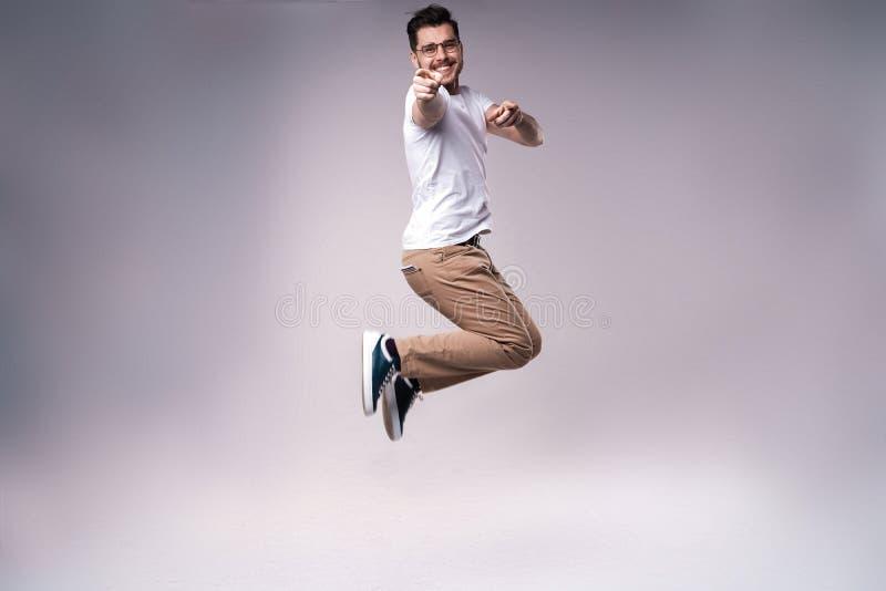 帅哥便服庆祝和跳跃在灰色背景 免版税库存图片