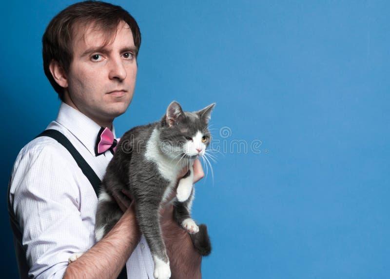 帅哥和拿着逗人喜爱的灰色和白色猫的蝶形领结侧视图桃红色衬衣的 免版税库存照片