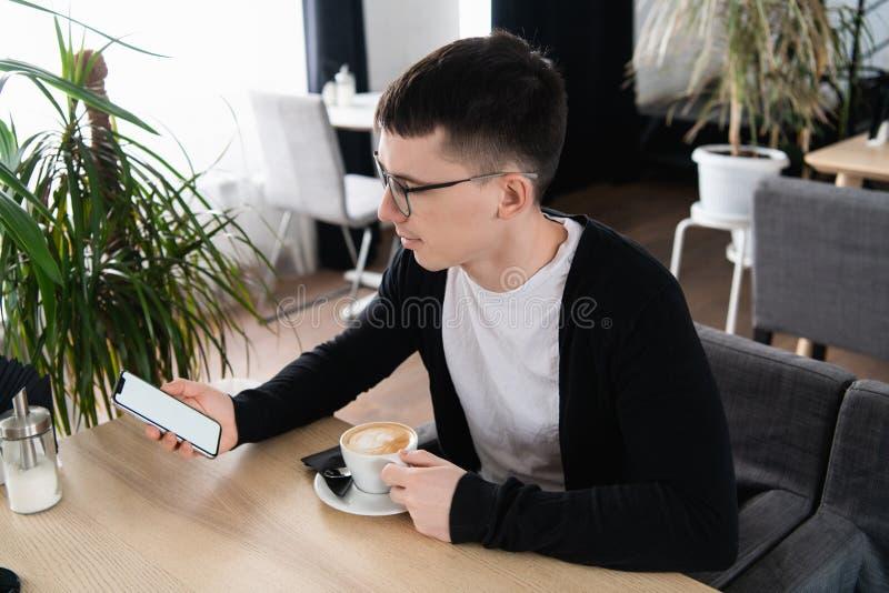 帅哥戴着眼镜的照片看一个手机的屏幕的 人坐在桌上  免版税库存图片
